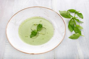 Cold cucumber soup with basil, green on a white wooden background, top view